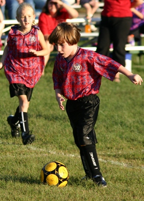 Two small children participating in a soccer game while spectators look on