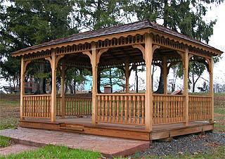 A wooden gazebo structure in a wooded area of a city park