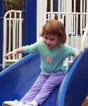 A girl going down a slide on a playground at a city park